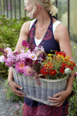 Woman holding basket with summer flowers