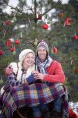 Couple sitting under christmas tree