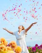 Lady throwing dahlia petals