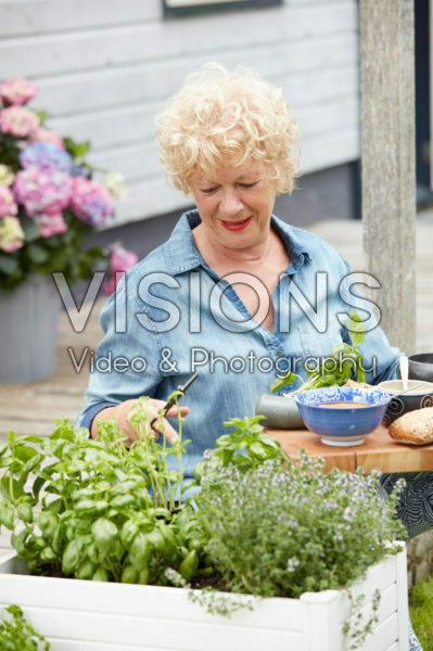 Lady cutting herbs