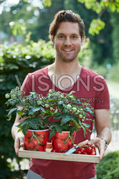 Man holding tomato plants